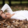 Beautiful girl lies on the earth, oak le — Stock Photo