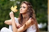 Beautiful young woman in autumn park — Stok fotoğraf