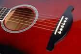 Red acoustic guitar — Stock Photo