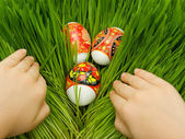 Easter eggs in the grass and hands — Stock Photo