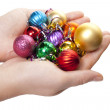 Hand and christmas toy decoration - Stock Photo