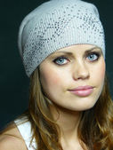 Blue-eyed girl in a grey cap with pastes — Stock Photo