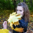 Girl holds yellow leaves in a hand — Stock Photo #1302884