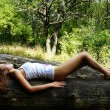 Girl has a rest on a log — Stock Photo #1303622