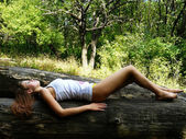 Girl has a rest on a log — Stock Photo