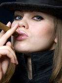 Beautiful lady in black and a cigar — Stock Photo