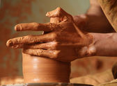 Hands of potter do a clay pot — Stok fotoğraf