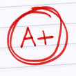 A+ grade written on a test paper. — Stockfoto