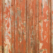 Foto Stock: Orange flaky paint on wooden fence.