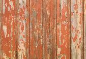 Oranje vlokkig verf op een houten hek. — Stockfoto