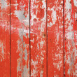 Stockfoto: Red flaky paint on wooden fence.