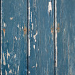 Stockfoto: Blue flaky paint on wooden fence.