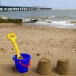 Kids bucket, spade and sandcastles. - Stock Photo