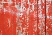 Peinture feuilletée rouge sur une clôture en bois. — Photo