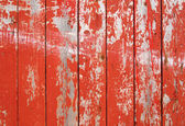 Red flaky paint on a wooden fence. — Zdjęcie stockowe