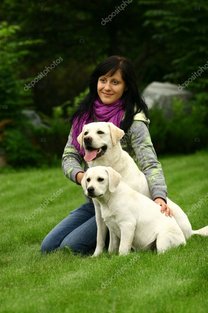 The girl sits on a green grass with two white dogs — Stock Photo #1511784