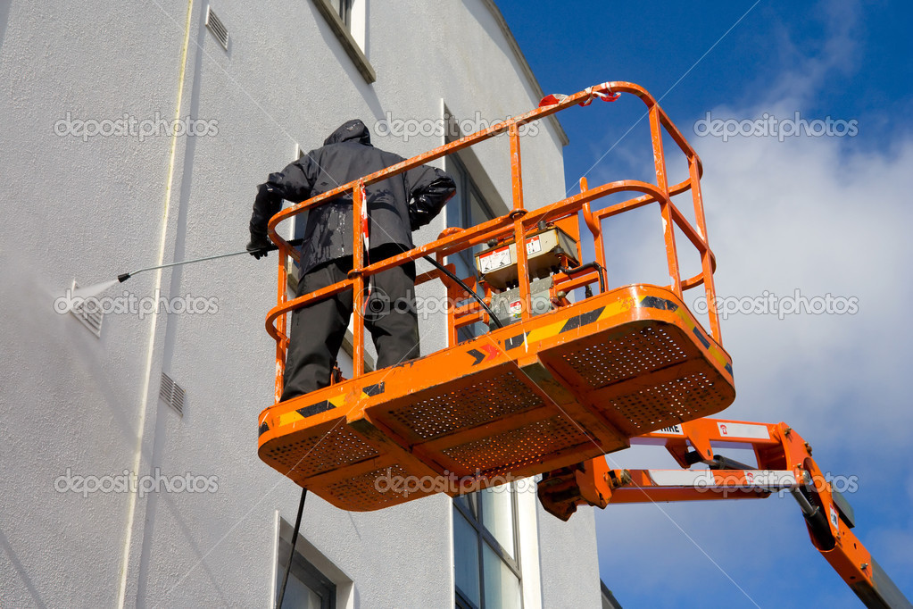 Worker In Cherry-picker Washing A building Wallwith high presure device  Foto Stock #1143569