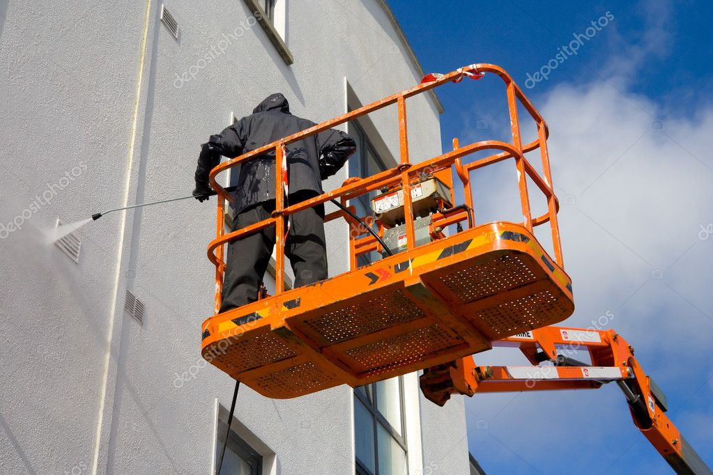 Worker In Cherry-picker Washing A building Wallwith high presure device — Stockfoto #1143569