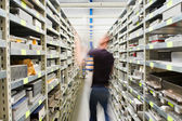 Technician and shelves with spare parts — Stock Photo