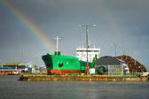 Cargo ship in docks and rainbow — Stock Photo