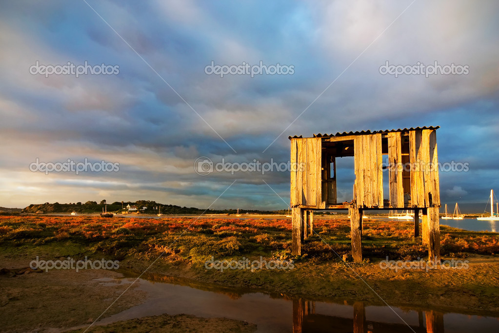 Sunset landscape with old fishing hut and stormy clouds — Stock Photo #1290300