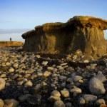 Lone cliff on stony beach and man — Stock Photo