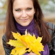 Happy girl with yellow leaves and smiles — Stock Photo #1209089