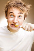 A funny young man cleans teeth. Toned. — Stock Photo