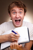 A funny young man writes in a notebook — Stock Photo
