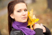 Portrait of young woman in autumn park. — Stock Photo