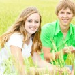 Stock Photo: Happy Teens in field. Focus on girl.