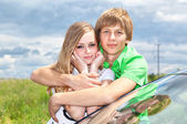 Girl and boy at the car in the field — Stock Photo