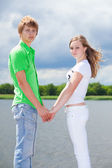 Teen boy and girl holding hands — Stock Photo
