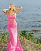Beautiful girl in a long pink dress. — Stock Photo