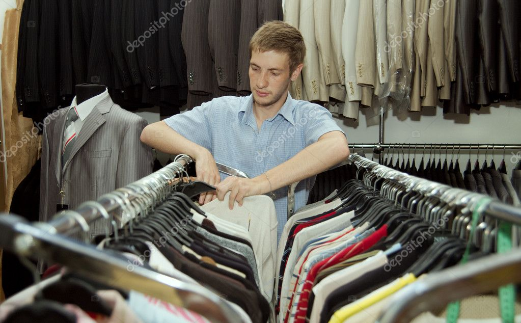The young man chooses to itself clothes in a supermarket. — Stock Photo #1218764