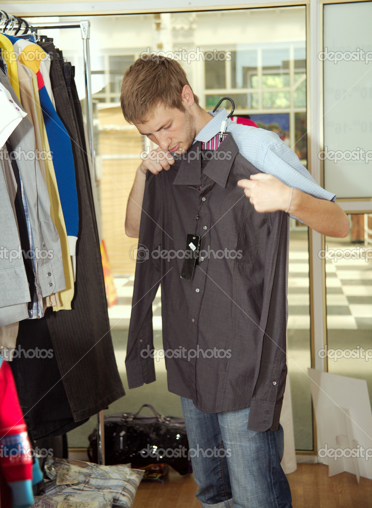 The young man chooses to itself clothes in a supermarket. — Stock Photo #1218863