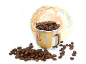 Cup with coffee beans and sauser — Stock Photo