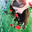 Royalty-Free Stock Photo: Beautiful brunette smelling poppies