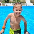 Young boy coming up of swimming pool — Stock Photo