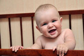 Baby holding bed grating — Stock Photo