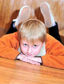 Little boy laying on the wooden floor — Stock Photo