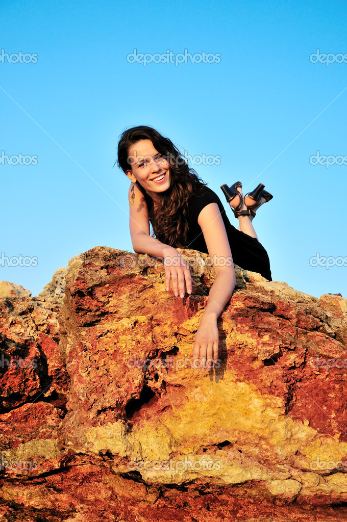 Beautiful girl is laing on the top of cliff  Stock Photo #1437828