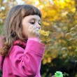 Little girl blowing soap bubbles — Stock Photo #1459287