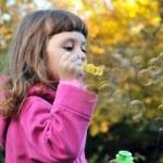 Little girl blowing soap bubbles — Stock Photo #1459287