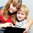Sister teaching brother using notebook — Stock Photo