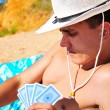 Man plying cards on the beach — Stock Photo