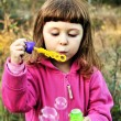 Girl blowing soap bubbles — Stok fotoğraf