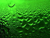 Green glass with drops — Stock Photo