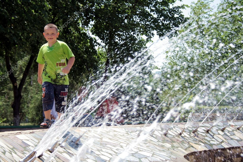 Fountain. Boy under the sprays of the water.   Stock Photo #2098507