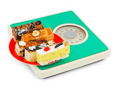 Cakes on weight scale — Stock Photo